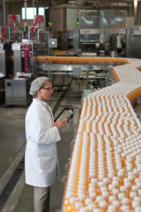 Man inspecting orange juice bottles at bottling plantの写真素材 [FYI03642963]