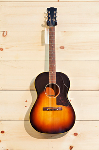 Acoustic guitar with label isolated on a wood grain wallの写真素材 [FYI03642973]