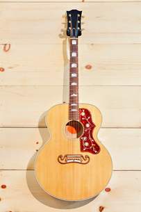 Acoustic guitar with label on a wood grain wallの写真素材 [FYI03642974]
