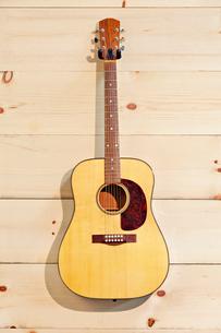 Steel-string acoustic guitar on wood grain wallの写真素材 [FYI03642976]
