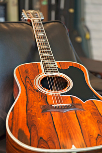 Close-up view of acoustic guitar lying on sofa in music storの写真素材 [FYI03642994]
