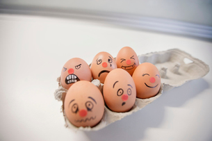 Six-pack eggs with faces painted in a egg cartonの写真素材 [FYI03643044]