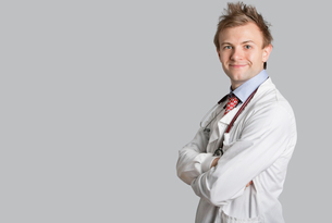 Portrait of a male doctor smiling with arms crossed over graの写真素材 [FYI03643058]