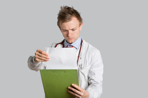 Male doctor reading medical records over gray backgroundの写真素材 [FYI03643059]