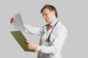 Male doctor in a lab coat reading medical records over grayの写真素材 [FYI03643061]