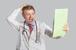 Male doctor terrified looking at medical reports over gray bの写真素材 [FYI03643062]