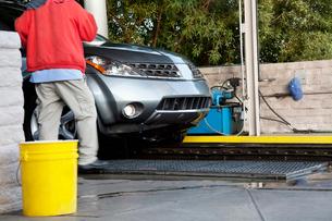 Car wash employee with vehicle on conveyor beltの写真素材 [FYI03643068]
