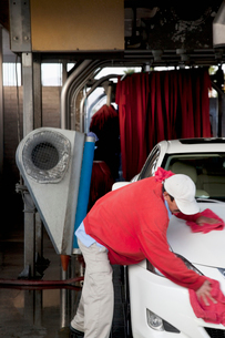 Employee wiping vehicle after washing in car washの写真素材 [FYI03643072]