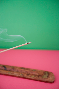 Close-up view of incense stick burning over colored backgrouの写真素材 [FYI03643085]