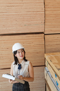 Young female industrial worker inspecting wooden planksの写真素材 [FYI03643096]