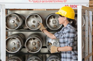 Female industrial worker taking out propane cylinderの写真素材 [FYI03643099]