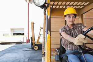Female industrial worker driving forklift truckの写真素材 [FYI03643107]