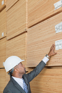 African American male engineer inspecting wooden planksの写真素材 [FYI03643112]