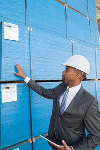 African American male contractor inspecting wooden planks whの写真素材 [FYI03643116]