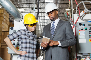 Female industrial worker and male engineer in discussion atの写真素材 [FYI03643120]