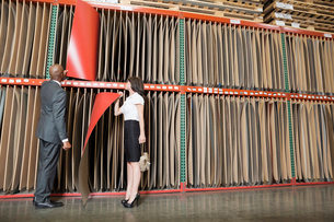 Multiethnic business coworkers selecting thin red veneer sheの写真素材 [FYI03643122]