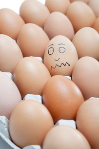 Funny face drawn on an egg surrounded by plain brown eggs inの写真素材 [FYI03643128]