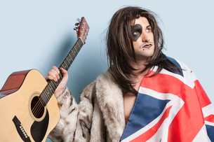 Young man with British flag holding guitar against light bluの写真素材 [FYI03643141]