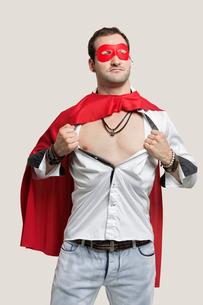 Young man in superhero costume standing against gray backgroの写真素材 [FYI03643167]