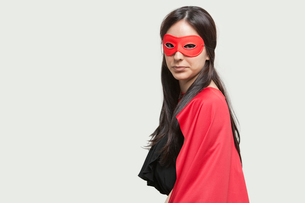 Portrait of young woman in superhero costume against gray baの写真素材 [FYI03643172]