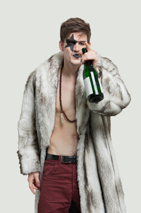 Portrait of young man with beer bottle over gray backgroundの写真素材 [FYI03643180]