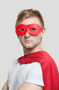 Portrait of young man wearing superhero costume against grayの写真素材 [FYI03643182]