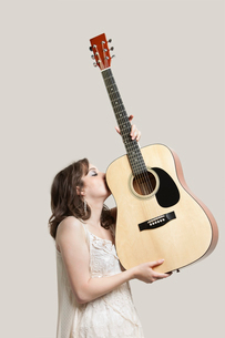 Young woman kissing guitar against gray backgroundの写真素材 [FYI03643183]