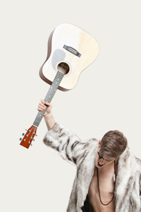 Frustrated young man in fur coat about to throw his guitar aの写真素材 [FYI03643185]