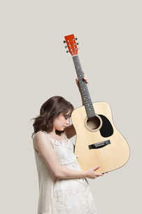 Young woman holding guitar against gray backgroundの写真素材 [FYI03643187]