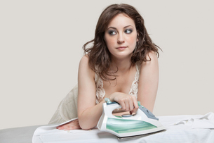 Young woman looking away while ironing shirt over gray backgの写真素材 [FYI03643190]