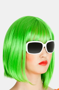 Young woman wearing green wig over gray backgroundの写真素材 [FYI03643211]