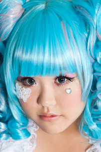 Portrait of cute woman wearing blue wig over gray backgroundの写真素材 [FYI03643217]