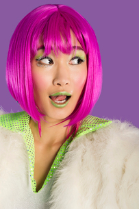 Surprised young funky woman in pink wig looking sideways oveの写真素材 [FYI03643219]