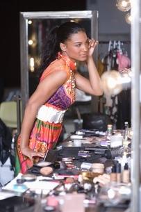 Woman applies makeup in dressing room mirrorの写真素材 [FYI03643221]