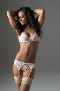 Woman stands in underwear and suspendersの写真素材 [FYI03643226]