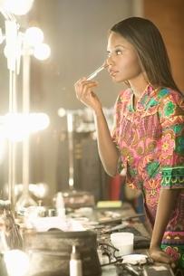Woman stands applying makeup in dressing room mirrorの写真素材 [FYI03643229]