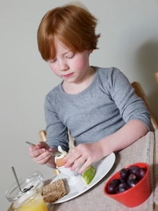 7-8 year old sits eating boiled eggの写真素材 [FYI03643238]