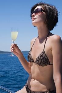 Brunette woman sits on deck in bikiniの写真素材 [FYI03643295]
