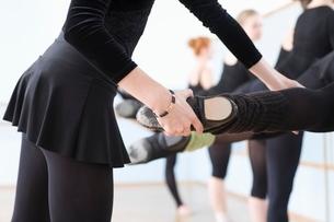 Ballet teacher adjusts foot positions at the barreの写真素材 [FYI03643310]