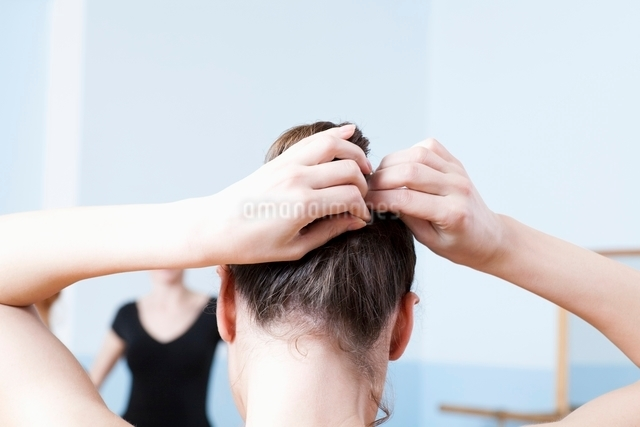 Young woman adjusts hair during ballet classの写真素材 [FYI03643318]