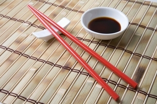 Red chopsticks and side bowl of soy sauceの写真素材 [FYI03643332]