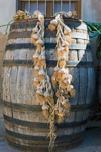 String of garlic hanging from wooden caskの写真素材 [FYI03643344]