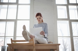 Woman sits on desk with laptop in loft apartmentの写真素材 [FYI03643379]