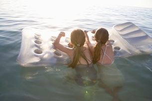 Twin sisters on air bed in evening lightの写真素材 [FYI03643385]