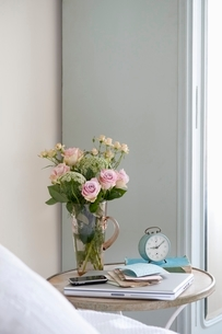 Roses in vase on bedside table with books and alarm clockの写真素材 [FYI03643406]