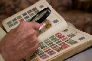 Senior man looks at stamp collection with magnifying glassの写真素材 [FYI03643475]