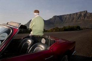 Senior man admires view leaning on vintage racing car on Sigの写真素材 [FYI03643476]