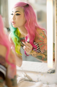 Reflection of a young woman in mirror applying lipstickの写真素材 [FYI03643503]