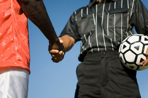Soccer player and referee shaking hands mid sectionの写真素材 [FYI03643509]