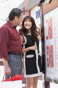 Smiling Couple standing near information sign on Shopping Trの写真素材 [FYI03643515]